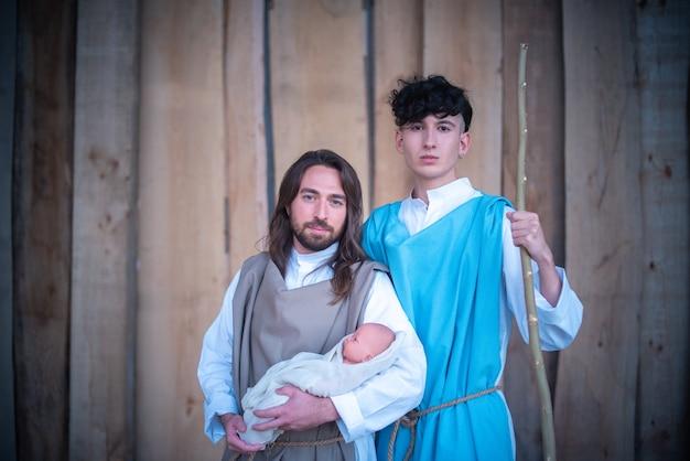 Portrait d'hommes homosexuels face caméra tout en représentant deux personnages bibliques dans une crèche