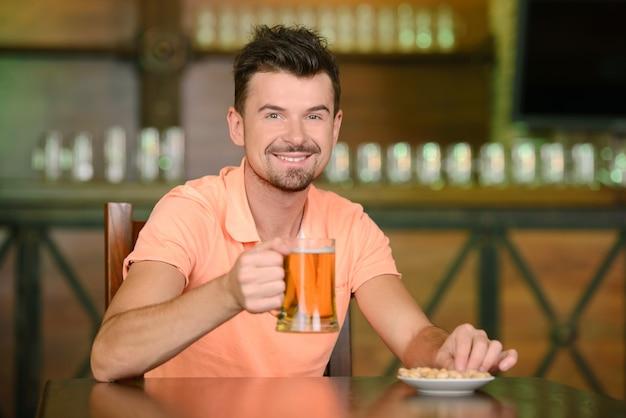 Portrait d'hommes joyeux buvant de la bière au bar.