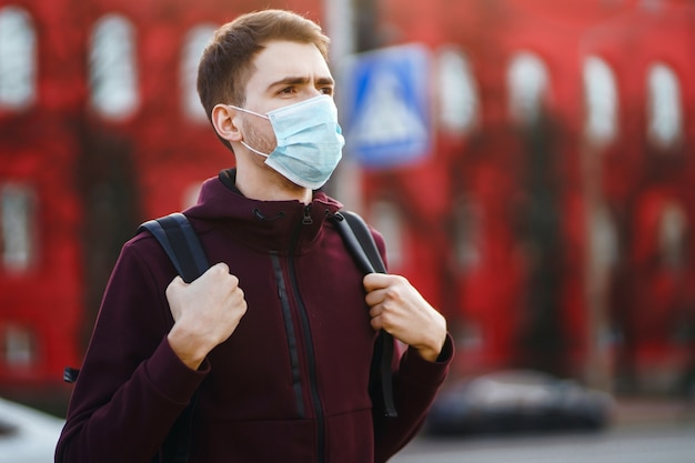 Portrait d'hommes en masque médical stérile protecteur sur son visage dans la ville de rue. covid19.