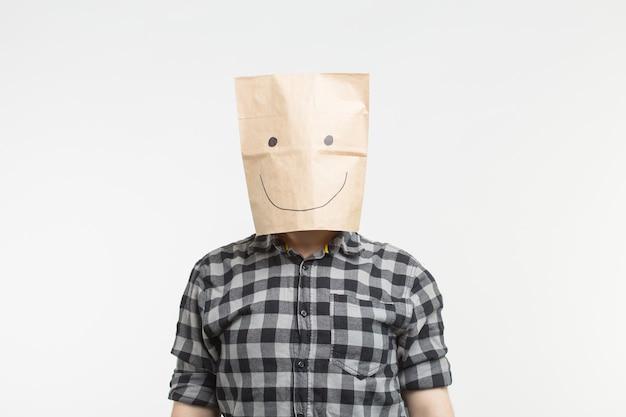 Portrait d'hommes en masque de sac en papier heureux sur fond blanc