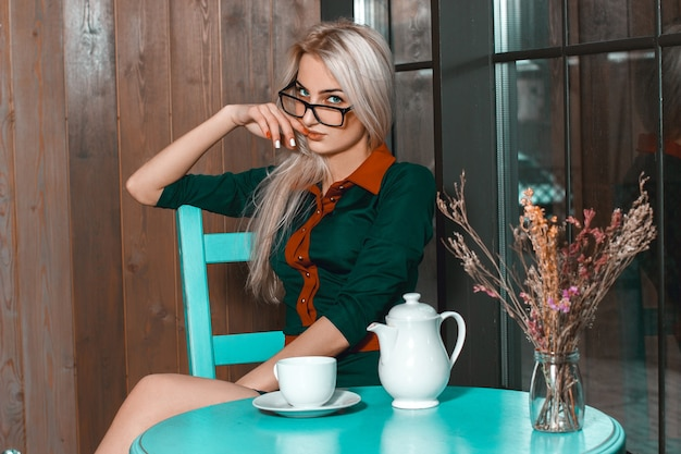 Portrait horizontal de la belle jeune femme dans un café avec une tasse de thé. belle fille avec une tasse de café au café à la recherche directe.