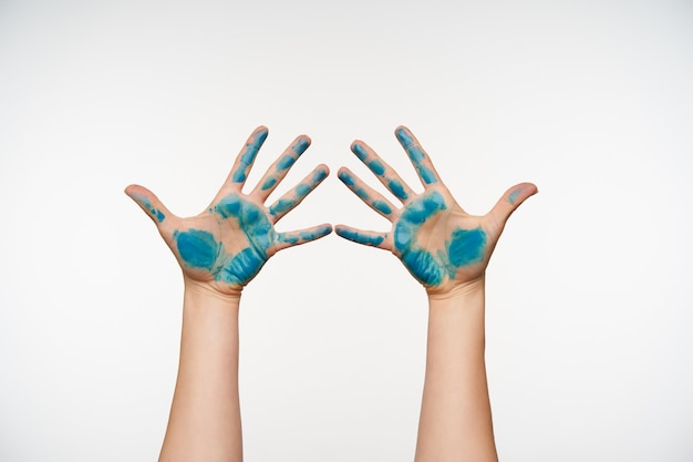 Portrait horizontal des bras de la femme surélevés peints en bleu en gardant tous les doigts séparément tout en posant sur blanc concept de langage corporel