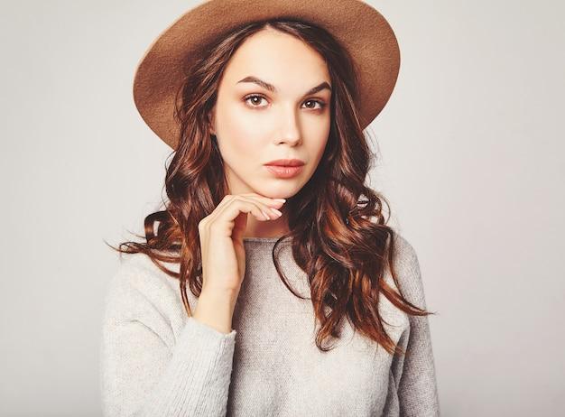 Portrait horizontal d'un élégant modèle féminin attrayant porte des vêtements d'été et un chapeau brun avec du maquillage naturel