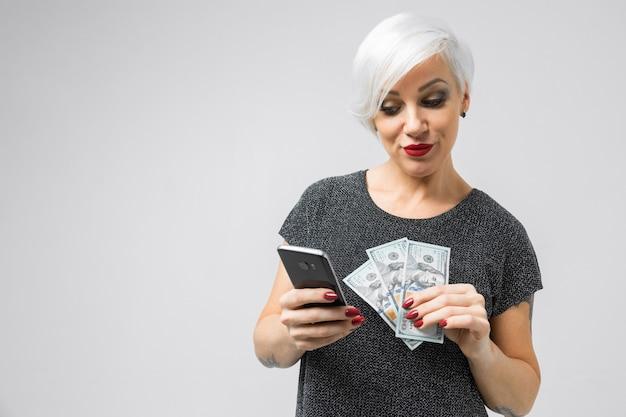Portrait horizontal d'une femme blonde adulte avec smartphone et lot d'argent