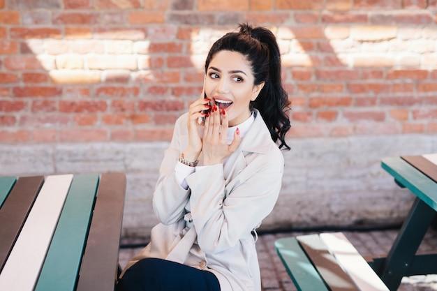 Portrait horizontal d'une femme heureuse avec les cheveux noirs et belle apparence habillé formellement