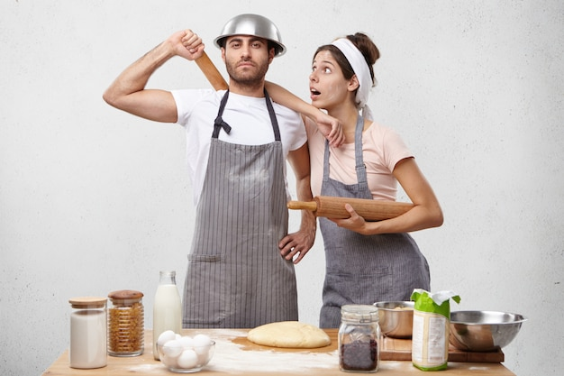 Portrait horizontal de femme surprise se penche sur l'épaule du mari étant choqué qu'il ne soit pas fatigué