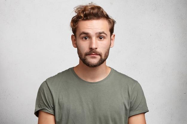 Portrait horizontal d'un homme de race blanche attrayant avec barbe et moustache regarde sérieusement