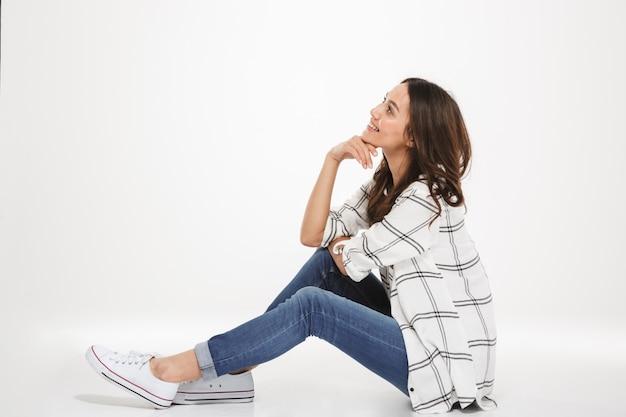 Portrait horizontal de jeune femme souriante aux cheveux bruns assis de profil sur le sol et soutenant la tête avec la main, isolé sur mur blanc