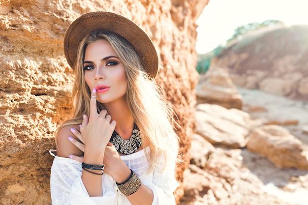 Portrait horizontal de jolie fille blonde aux cheveux longs posant à la caméra sur la plage sur fond de pierre.