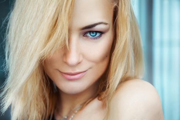 Portrait horizontal de sexy jeune fille blonde adulte aux yeux bleus.