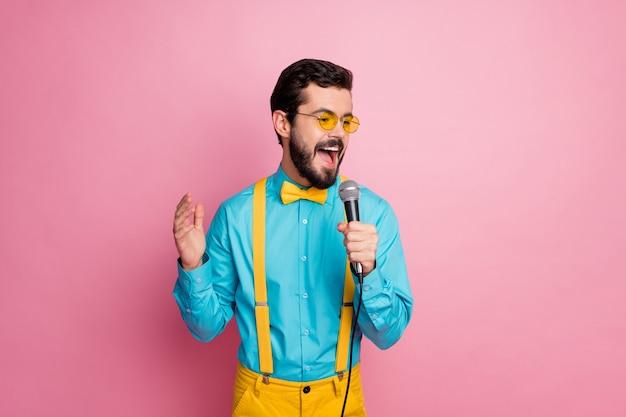 Portrait d'imposant barbu chantant karaoké tenir microphone
