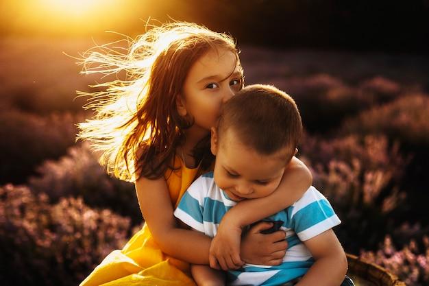 Portrait d'une incroyable petite fille vêtue d'une robe jaune embrassant et embrassant son petit frère sur la tête tout en regardant la caméra contre le coucher du soleil incroyable.