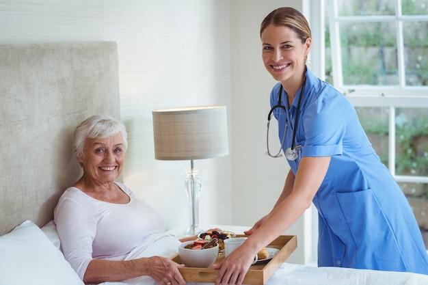 Portrait, de, infirmière souriante, donner nourriture, à, femme aînée