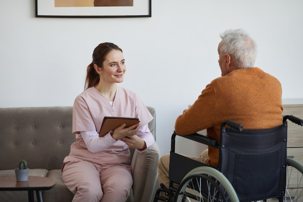 Portrait d'une infirmière souriante parlant à un homme âgé en fauteuil roulant et utilisant une tablette numérique à la maison de retraite, espace pour copie