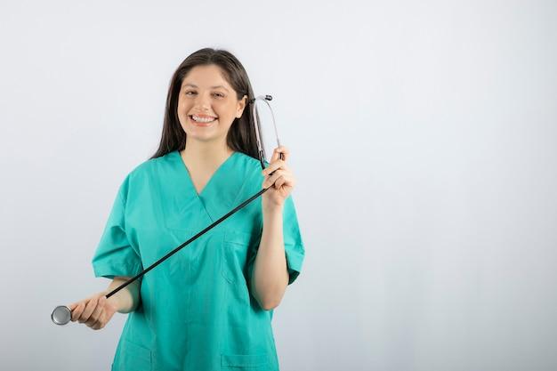 Portrait d'infirmière avec stéthoscope posant sur blanc.