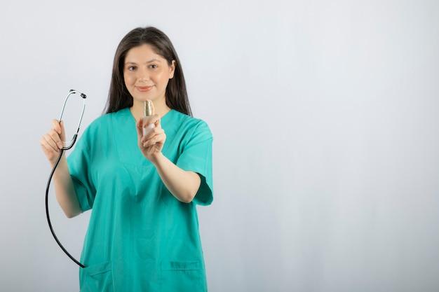 Portrait d'infirmière tenant un stéthoscope sur blanc.