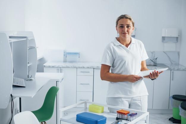 Portrait d'infirmière en uniforme blanc qui se dresse dans la salle de la clinique moderne.