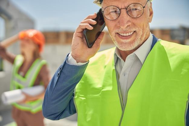 Portrait d'un ingénieur civil joyeux à lunettes appelant son téléphone portable à l'extérieur