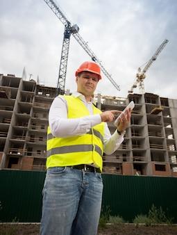 Portrait d'ingénieur en construction souriant posant avec une tablette numérique