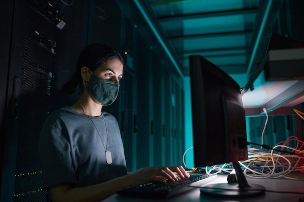 Portrait d'une ingénieure informatique portant un masque tout en utilisant un ordinateur et travaillant dans la salle des serveurs éclairée par la lumière bleue, espace de copie