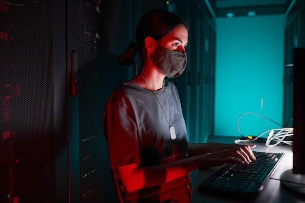 Portrait D'une Ingénieure Informatique Portant Un Masque Tout En Utilisant Un Ordinateur Et Travaillant Dans La Salle Des Serveurs éclairée Par La Lumière Rouge, Espace De Copie Photo Premium