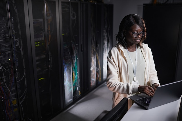 Portrait d'une ingénieure réseau afro-américaine utilisant un ordinateur portable tout en travaillant dans une salle de serveur sombre, espace de copie