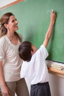 Portrait d'une institutrice aidant un écolier à faire un additio