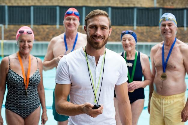 Portrait de l'instructeur avec des hommes et des femmes seniors au bord de la piscine
