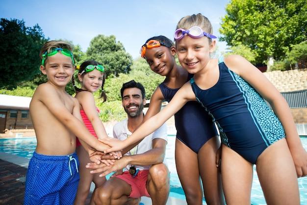 Portrait de l'instructeur masculin et des enfants empiler les mains au bord de la piscine