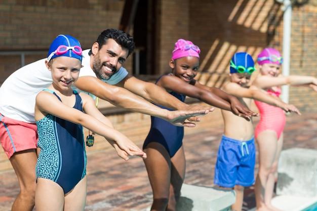 Portrait de l'instructeur masculin et des enfants se préparant à sauter dans la piscine