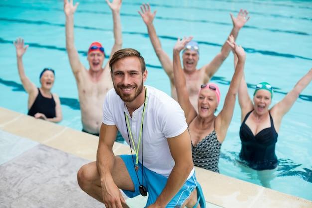 Portrait d'un instructeur masculin avec des nageurs seniors insouciants dans la piscine