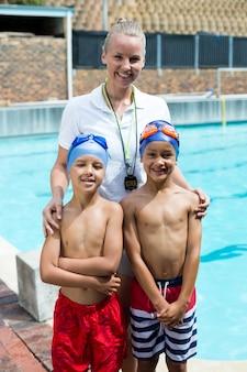 Portrait d'instructeur de natation avec des garçons au bord de la piscine