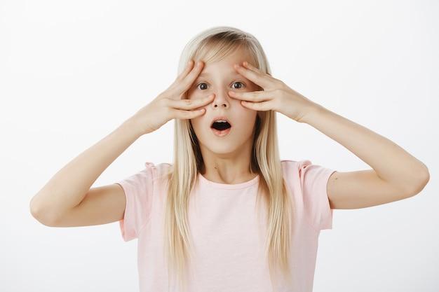 Portrait intérieur d'une adorable fille blonde surprise choquée en t-shirt rose, laissant tomber la mâchoire, disant wow tout en tenant les doigts près des yeux