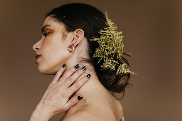 Portrait intérieur de belle fille avec plante aux cheveux noirs. dame blithesome élégante posant sur un mur marron.
