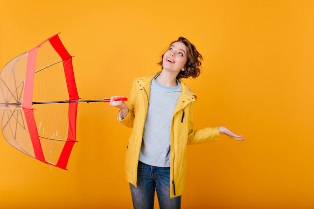 Portrait intérieur de charmante jeune fille à la recherche par temps de pluie. femme pâle caucasienne en veste jaune posant avec parasol et expression du visage heureux.