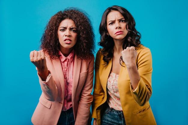 Portrait intérieur de deux femmes agitant leurs poings