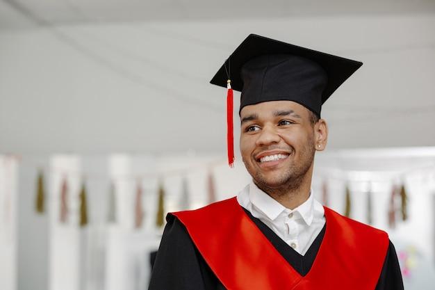 Portrait d'intérieur d'un étudiant noir souriant portant une robe de graduation et une casquette carrée avec un pompon rouge de la classe de 2021