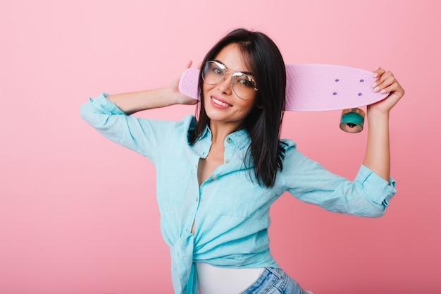 Portrait intérieur d'une femme asiatique spectaculaire en chemise de coton et lunettes de soleil. modèle féminin latin aux cheveux noirs avec longboard souriant dans la chambre rose.