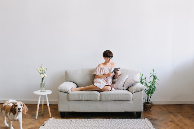 Portrait intérieur d'une fille amusée avec une coiffure courte à l'aide de la tablette tandis que son chien beagle se promène autour du canapé