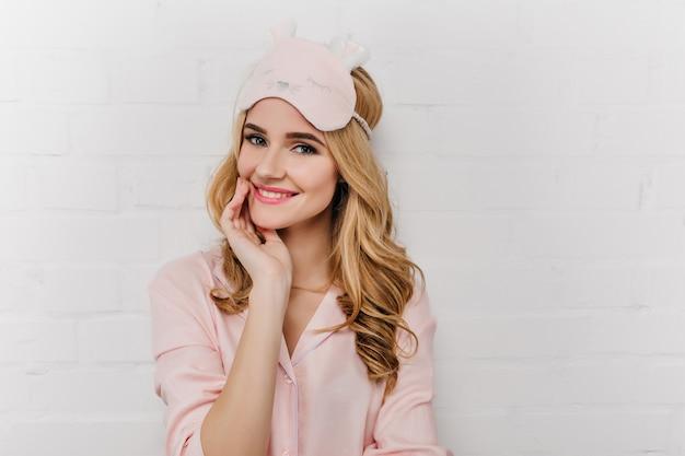 Portrait intérieur d'une fille blonde glamour dans un masque de sommeil mignon. superbe jeune femme porte un pyjama rose posant sur un mur blanc.