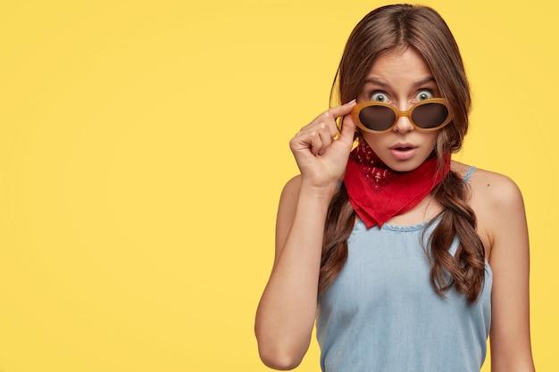 Portrait intérieur d'une fille choquée voit quelque chose d'incroyable, regarde à travers des lunettes de soleil