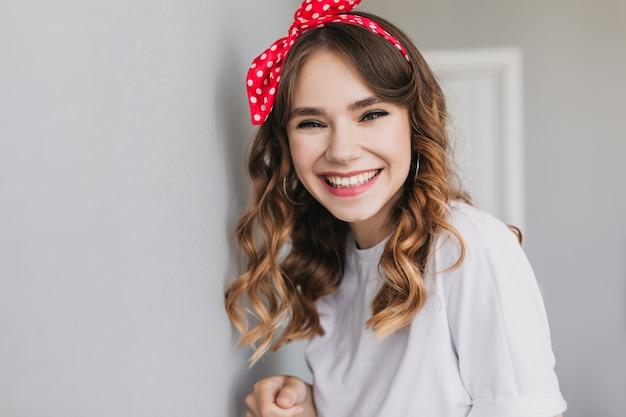 Portrait intérieur d'une fille élégante posant avec un sourire heureux. debonair curly femme caucasienne exprimant le bonheur.