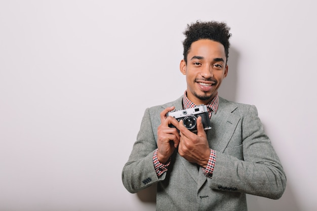 Portrait intérieur d'heureux homme afro-américain vêtu d'une veste grise tenant la caméra dans les mains sur fond gris