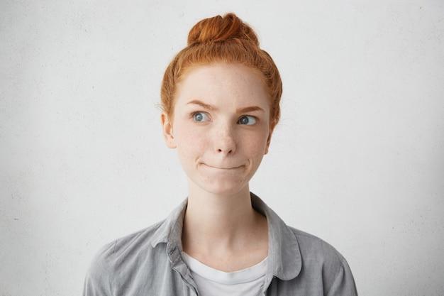 Portrait intérieur de jeune femme d'apparence extraordinaire à la recherche de côté avec un regard pensif en levant ses sourcils roux et en appuyant sur les lèvres la planification de sa réunion en essayant de décider quelque chose d'important