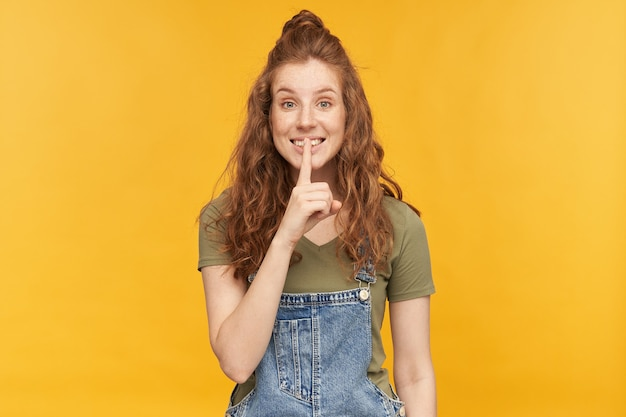 Portrait intérieur d'une jeune femme rousse portant une salopette en jean bleu et un t-shirt vert qui sourit largement, flirte avec quelqu'un et montre un geste de silence
