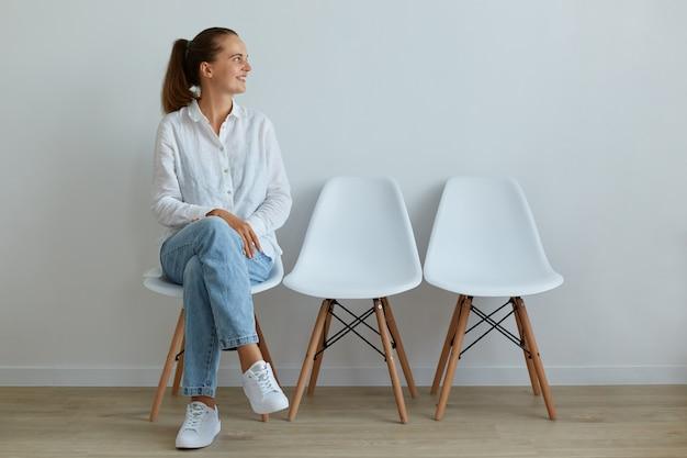Portrait intérieur d'une jeune femme séduisante assise sur une chaise dans la salle d'attente, vêtue d'un jean et d'un t-shirt blanc, détournant les yeux avec un sourire charmant, exprimant des émotions positives.