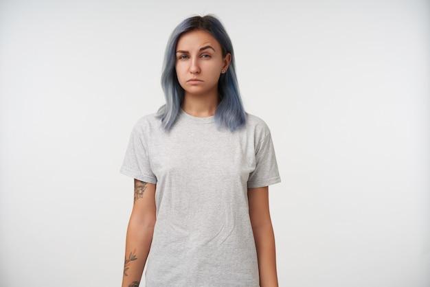 Portrait intérieur de jeune femme tatouée plissant les yeux tout en regardant avec suspicion et en gardant ses mains le long du corps tout en posant sur blanc