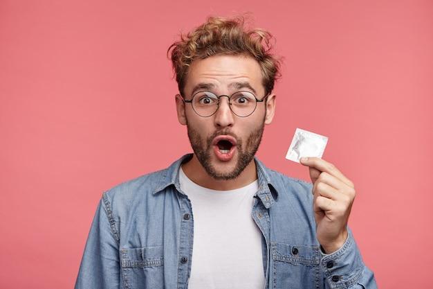 Portrait intérieur de jeune homme barbu avec une coiffure à la mode