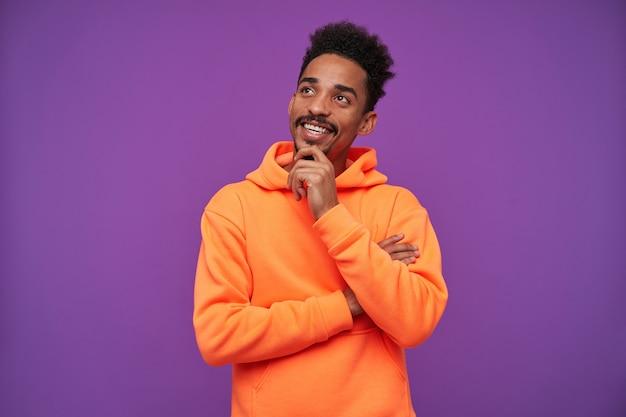 Portrait intérieur de jeune homme brune barbu aux yeux bruns positif avec une peau foncée tenant son menton et souriant rêveusement tout en posant sur violet dans des vêtements décontractés sportifs