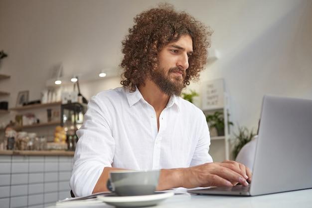 Portrait intérieur de jeune pigiste frisé attrayant avec barbe regardant l'écran attentivement, travaillant dans un lieu public à l'aide du wi-fi, portant une chemise blanche